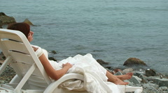 Young Woman In White Dress Lying On Chaise-Longue Stock Footage