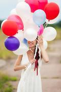 portrait of happy smiling wooman hiding latex balloons - stock photo