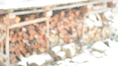 Falling snow against firewood pile. Shallow dof. Stock Footage
