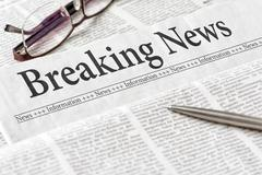 A newspaper with the headline Breaking News - stock photo