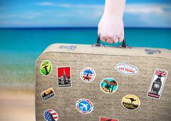 hand holds a suitcase with stickers - stock photo