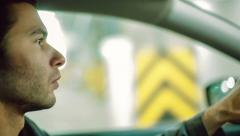 A man driving the car at undergroung parking. Close up. Bokeh background Stock Footage