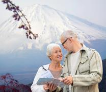 Happy senior couple with travel map over mountains Stock Photos
