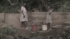 Africa poor African girls fill and carry water bucket pan Stock Footage