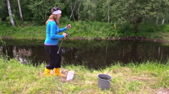 Pregnant woman in yellow boots catch fish. cat sit near bucket Stock Footage