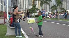 Boy buying a snack on La Cinta Costera, Panama City, Panama Stock Footage