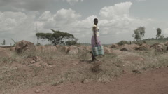 Africa woman walking in African landscape pan Stock Footage