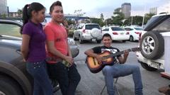 Young adults paying guitar. La Cinta Costera, Panama City, Panama Stock Footage