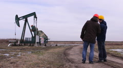 Talking about the plans, Gas pump worker pump oil jack working - stock footage