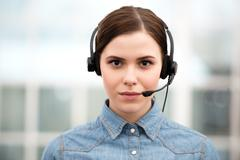 Beautiful call center female operator looking at camera - stock photo