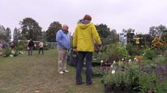 Customers look at plants seedlings sold in botanical market fair Stock Footage