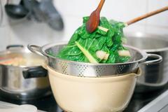 Blanching hot chard using kitchenware Stock Photos