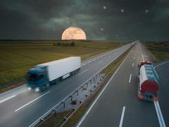 Trucks on highway at night of the full moon - stock photo