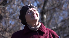 Senior Pensioner Woman Looking to the Sky in Park. 4K Stock Footage