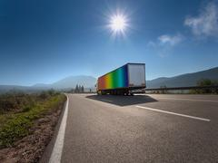 Truck in rainbow color on the highway - stock photo