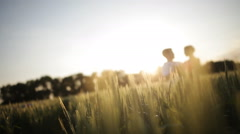 Young couple in a wheat field at sunset Stock Footage