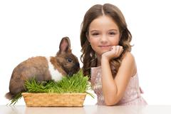 Girl sitting with cute bunny and looking at camera Stock Photos