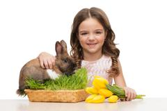 Beautiful girl sitting with bunny and tulips - stock photo