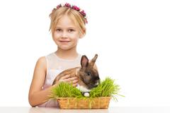 Little girl with little brown bunny in grass - stock photo
