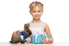 Girl and bunny are near blue present box - stock photo