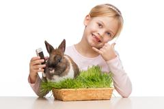 Girl with brown bunny in grass and telephone - stock photo