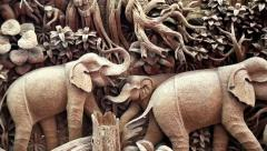 Picture with elephants made of one piece of wood at a teak factory in Thailand Stock Footage