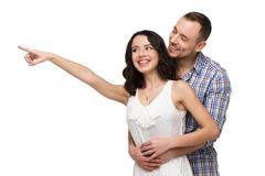 Happy lovers looking at something with interest Stock Photos