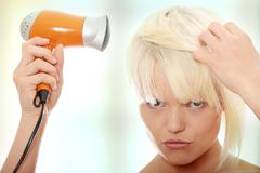 Blonde woman using hair drier - stock photo