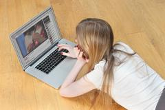 Teenage girl on laptop looking at YouTube videos Kuvituskuvat
