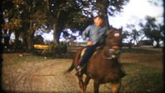 1901 - young farm boy rides a horse around the yard - vintage film home movie Stock Footage