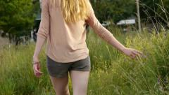 Closeup Of Young Woman's Hand, Touching Grass, She Smiles Over Her Shoulder - stock footage