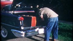 1902 - man & woman load 1956 Oldsmobile for trip - vintage film home movie Stock Footage
