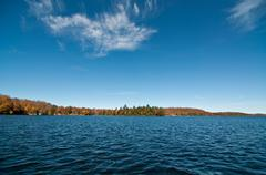 Canadian Lake with Autumn Colours and Blue Sky - stock photo