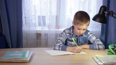 Child doing homework, writing in a notebook in the evening at the table in Stock Footage
