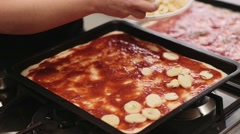 Woman applaying potatoes on the homemade pizza. Shot in slowmotion Stock Footage