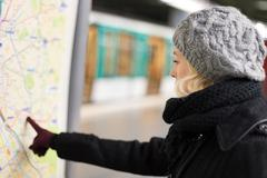 Lady looking on public transport map panel. Stock Photos