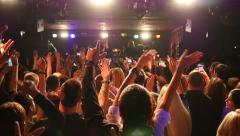 Cheering spectators listen to singer on the rock concert stage of dance club Stock Footage
