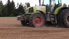 Tractor with special equipment fertilize sow field in summer Stock Footage