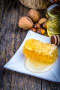 honey dipper and honeycomb, nuts of various kinds - stock photo