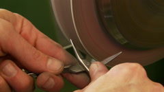 Hands honing a scissor blade on a honing wheel Stock Footage