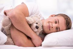 Young man lying under a blanket with teddy bear - stock photo