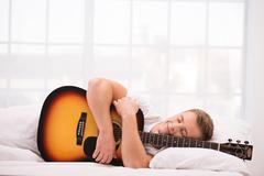 Young man lying in bed with guitar Stock Photos