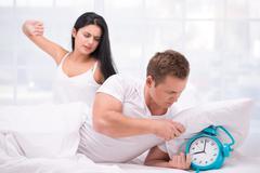 Sleepy couple waking up by an alarm clock ringing Stock Photos