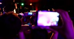 Cheering spectators make photo of singer on rock concert via smartphone - stock footage