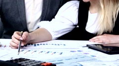 Successful people discussing business charts.  Each proves his point. Slow Stock Footage