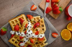 Stock Photo of Homemade waffles with maple syrup and strawberries