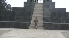 Man with the hat and coat climbing the stairs of the monument Stock Footage