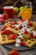 Homemade waffles with maple syrup and strawberries - stock photo