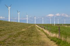 Windturbines along a dike in the Netherlands near a motorway - stock photo