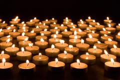 Large group of burning candles at a black background Stock Photos